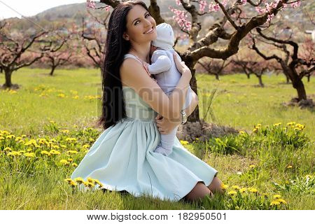 Woman In Elegant Dress Posing With Her Baby Boy In Blossom Garden