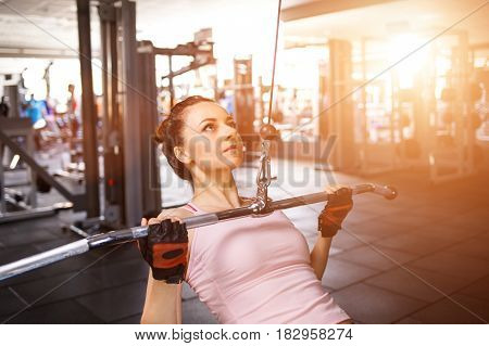 Young fitness woman performing close grip lat pulldown on cable machine