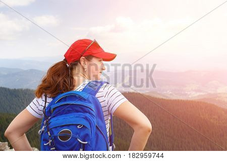 Young woman with blue backpack enjoying view from the top of mountain