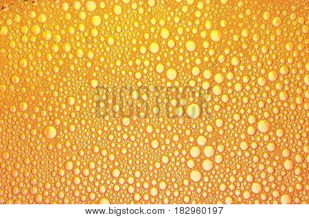 background of orange bubbles on the surface of the liquid