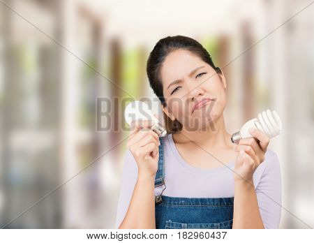 confused asian woman wearing jumpsuit holding light bulbs