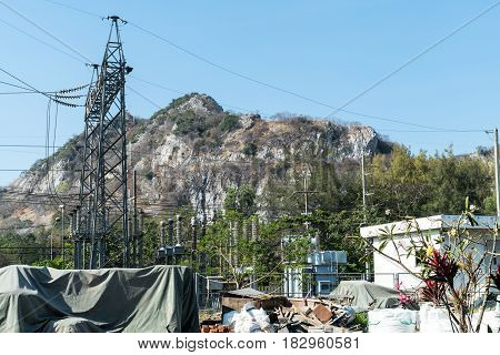 Power plant and Large electricity pole background with mountain