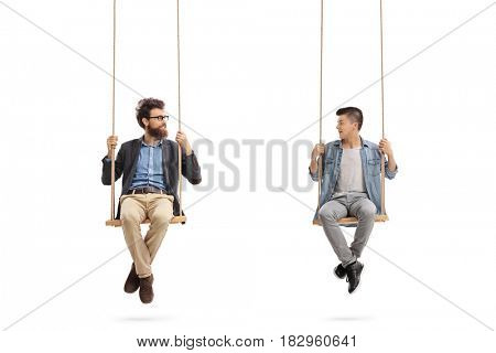 Father and son sitting on swings and looking at each other isolated on white background