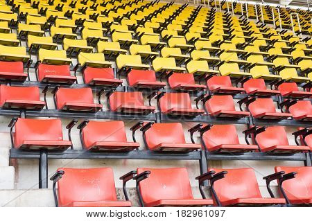 empty yellow and orange seats in stadium