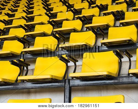 empty yellow seats in a row in stadium