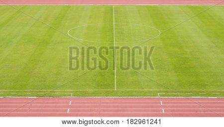 green soccer field with line and racecourse