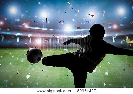 silhouette soccer player kicking the ball with stadium background