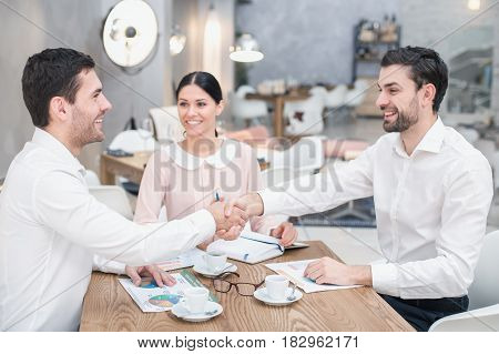 Business meeting. Business team discussing strategy. Businessmen and woman in luxury restaurant. They having coffee. Businessmen shaking hands
