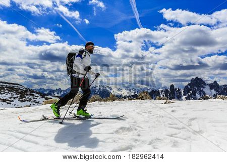 Mountaineer backcountry ski spring walking up along a snowy ridge with skis. In background blue cloudy sky and shiny sun and Tre Cime in South Tirol,