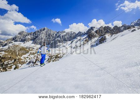 Mountaineer backcountry ski spring walking up along a snowy ridge. In background blue cloudy sky and shiny sun and Monte Cristallo in South Tirol, Dolomites, Italy. Adventure winter extreme sport.