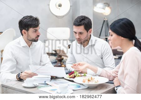 Business meeting. Business team discussing strategy. Businessmen and woman in luxury restaurant. They having meal and coffee
