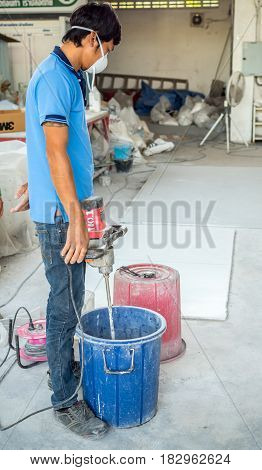 The worker prepairing to mix a mortar in blue bucket