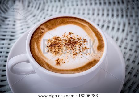 Cappuccino in white ceramic glass topping with powder