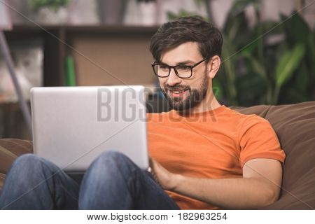 Young man programmer sitting on the sofa working with laptop