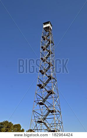A historic tall metal fire lookout tower stretches high into the blue sky.