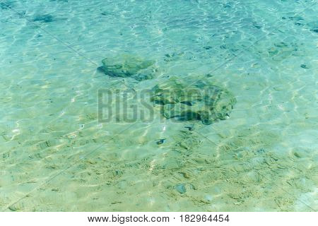 Clear blue sea water and the rock beneath it