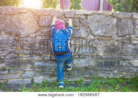 A Child Climbs A Fence.