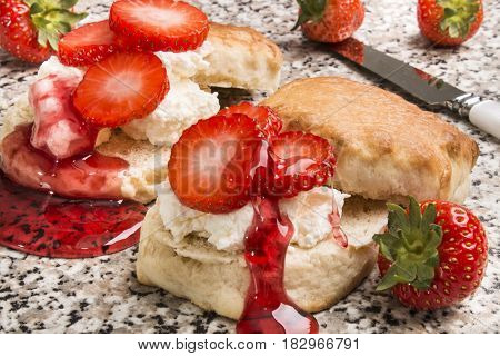 freshly baked scottish shortbread with whipped cream sliced strawberry and syrup