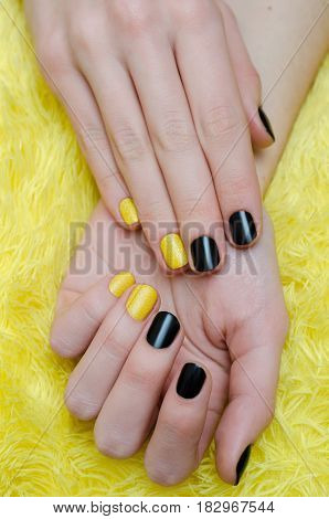 Nail art. Beautiful female hand with black and yellow manicure.