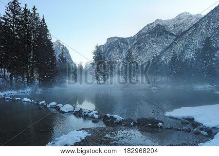 in mist gehuld winters meer en berg landschap