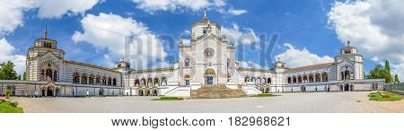 A huge wide panoram view of the entrance buildings of large monumental Cemetery in Milan, Lombardy, Italy. Bright summer day picture with colorful blue sky and white clouds