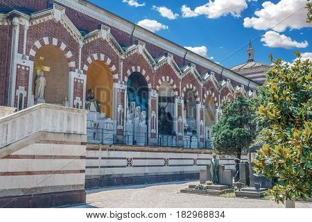 A side view of the entrance buildings of large monumental Cemetery in Milan, Lombardy, Italy. Bright summer day picture with colorful blue sky and white clouds