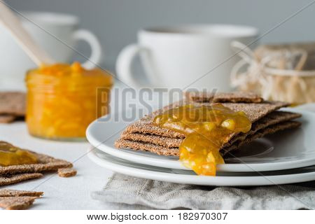 Closeup Of Brown Rye Crisp Bread (swedish Crackers) With Spread Orange Jam, On White Background. Swe