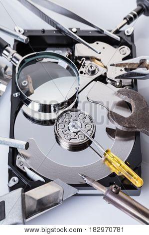 Disassembled computer hard disk and tools close-up