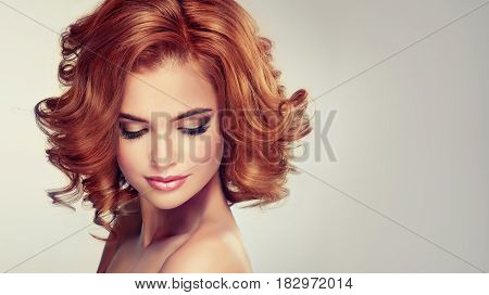 Beautiful girl model with short red curly hair . Woman styling curly hairstyle .