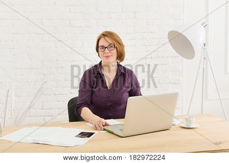Successful middle-aged businesswoman in the office. Woman using laptop computer and smartphone.
