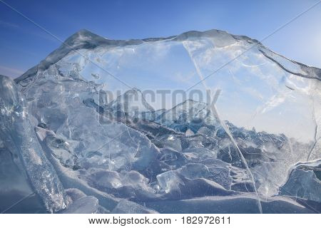 View on field of blue broken ice through the ice block on sky background