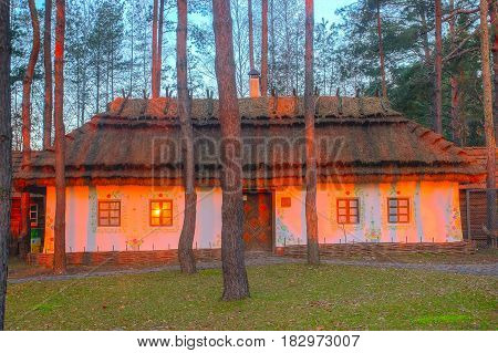 Ancient traditional ukrainian mud hut in forest morning