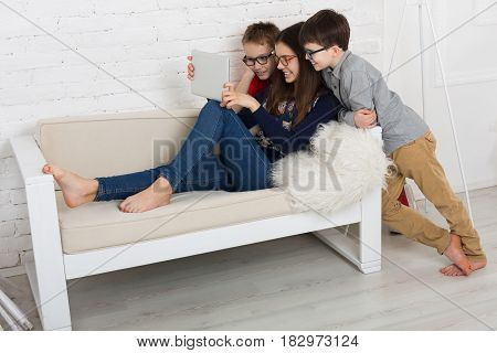 Children computer games, social networks and media addiction concept. Group of kids in eye glasses look into tablet. Girl and boys with device