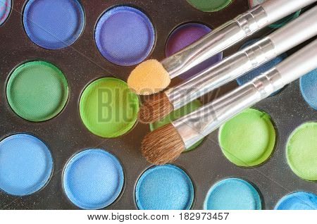 Three Brushes on the palette of eye shadows - blue, green. purple, colors