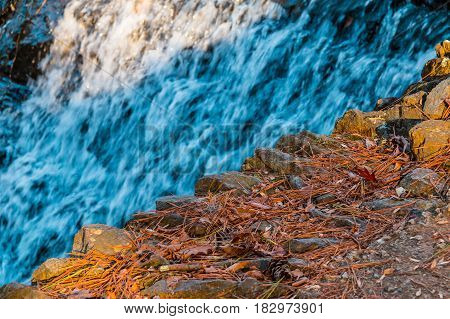 Spillway waterfall and stone edge closeup in sunny autumn day