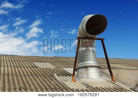 Kitchen chimney on the roof over cloudy blue sky