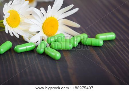 Green capsules and chamomile flowers on wooden table. The concept of alternative medicine and phytotherapy.