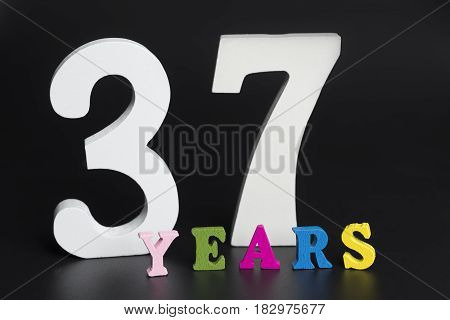 Letters and numbers thirty-seven years on a black isolated background.