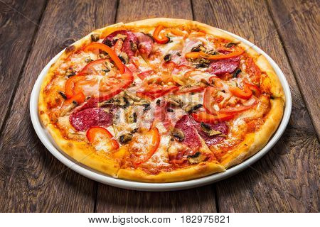 Delicious pizza with mushrooms, peppers, bacon and salami - thin pastry crust at wooden background