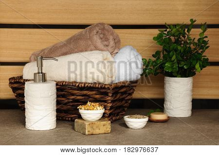 soapherbs sponge and towels in a wicker basket on a light background