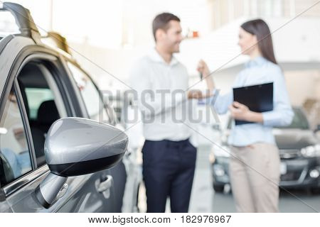 Young man and woman in a car rental service holding contract
