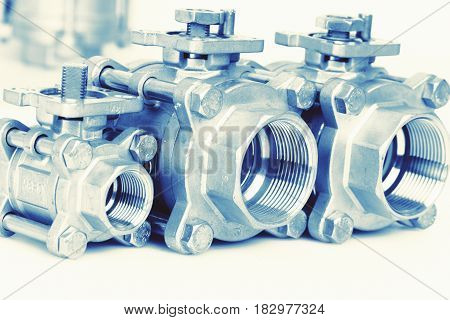 Group 3 valves different sizes ball valve with selective focus on thread fittings. Stainless steel valve