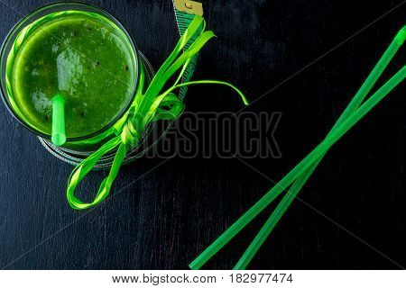Green Smoothie Near Centimeter  On Black Wooden Background. Diet. Detox. Healthy Drink. Top View.