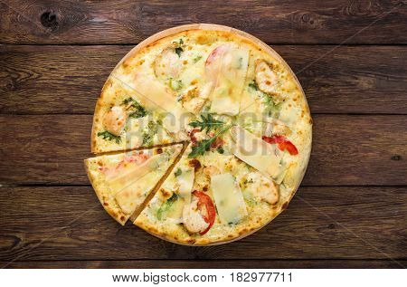 Delicious pizza top view on wood, with chicken, parmesan, tomatoes, white sauce and fresh arugula - thin pastry crust, piece cut off