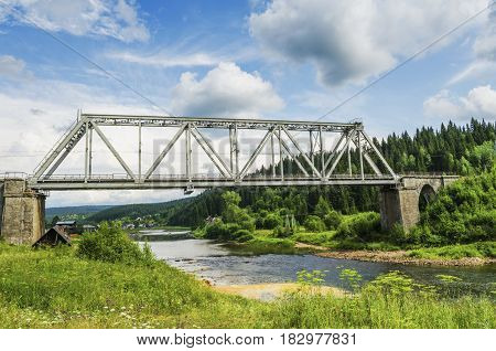 PERM KRAI RUSSIA - JULY 13 2016: Railway bridge through the river Usva on a summer day