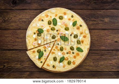 Italian seafood pizza with shrimps, thin pastry crust with slice cut, at wooden background, pizza delivery top view