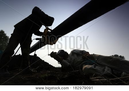 Silhouettes of two workers welding a pipe