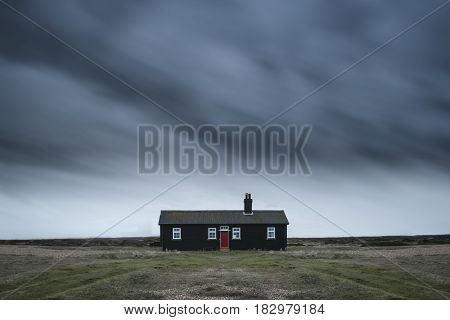 Remote Desolate Isolated House Under Dark Stormy Sky During Winter Landscape Conceptual Image
