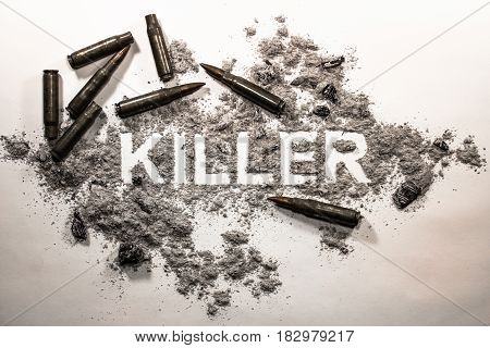 Killer text word written in grey ash dirt filth with bullets around as crime criminal murder war death violence victim weapon gun concept background