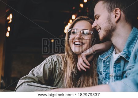 Portrait of beautiful young couple in love at a coffee shop. Gorgeous smiling girl in stylish eyeglasses leaning on her boyfriend's shoulder